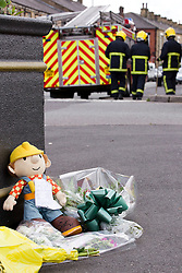 © Licensed to London News Pictures. 27/06/2012. Oldham , UK . A large explosion , believed to be caused by gas , has brought down at least one house in an Oldham terrace. A makeshift shrine dedicated to 2 year old Jamie Heaton who was killed in the blast including a Bob the Builder toy , with firemen in the background . Photo credit : Joel Goodman/LNP