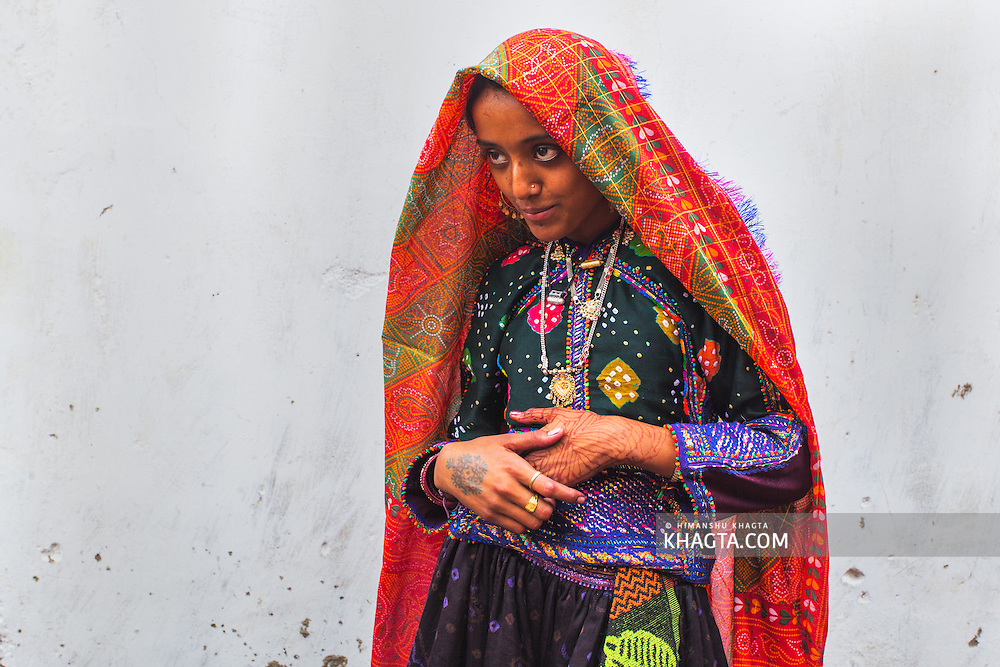 Portrait of a Gujarati girl wearing traditional costume standing outside the house of her friend in a village in Bhuj, Gujarat, India