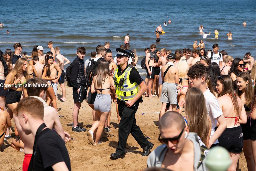 Edinburgh, Scotland, UK. 31 July, 2020. Temperature of 25C and sunshine brought huge crowds to Portobello Beach outside Edinburgh. Several large groups of teenagers were enjoying beach and alcoholic drinks were very popular. Iain Masterton/Alamy Live News