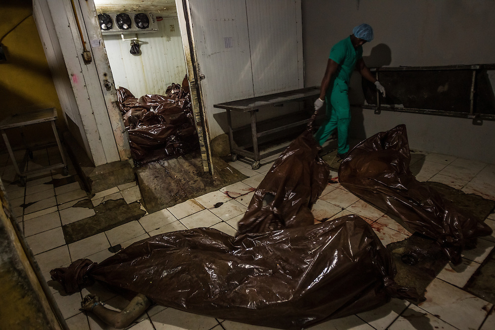 "SAN PEDRO SULA, HONDURAS - MAY 25, 2014:  A technician drags a body, wrapped in a brown garbage bag from the freezer, which is overflowing, with a massive heap of over 60 corpses, all from gunshots or other violent deaths, over a period of two days. Staff at the morgue reported regularly receiving corpses of children under ten years old that had been shot point-blank. They described a two-year old shot multiple times in the skull, and a four-year old girl that had her arms and legs chopped of with a machette. Many of the family members of murdered children told morgue staff that members of the Mara-18 gang extorted their family by threatening to kill their children if they didn't regularly pay them a set fee that they called a ""tax"". When the families refused or were unable to pay, they followed through on their threats. Many families arriving in migrant shelters in Mexico also report that Mara-18 gang members threatened to kill their children if they did not make large payments, and since they did not have the financial resources to pay them, they fled north with their children. PHOTO: Meridith Kohut for The New York Times"