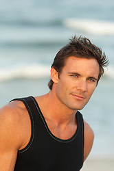 portrait of a dark haired blue eyed man at the beach
