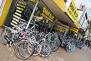 In Apeldoorn staan voor een fietswinkel nieuwe en tweedehands fietsen opgesteld.<br /> <br /> In Apeldoorn new and used bikes are lined up for a bike shop.