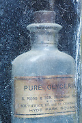 An old bottle a pure Glycerine in the window of a small clock repair shop in Highgate, London