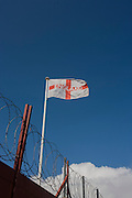 With coils of barded security wire beneath, a sad-looking English flag on a pole overlooks an industrial yard in south London.