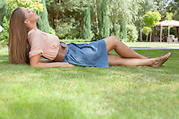 Full length side view of relaxed young woman lying on grass in park