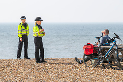 © Licensed to London News Pictures.10/04/2020. Brighton, UK. Police officers patrol the seafront in Brighton and Hove to stop members of the public sunbathing and relaxing on the beach as hot and sunny weather is hitting the seaside resort on the first day of the Easter Bank Holiday weekend and a full Coronavirus lockdown continues across the UK. Photo credit: Hugo Michiels/LNP