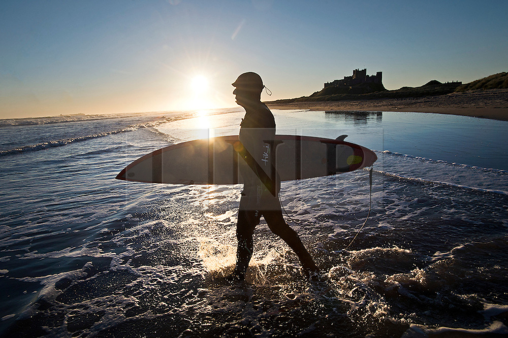 © Licensed to London News Pictures. 07/10/2012. Bamburgh, UK.  A surfer entering the sea at sunrise on Bamburgh beach  in Northumberland, UK on October 7, 2012. Photo credit : Ben Cawthra/LNP