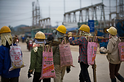Vietnamese workers come out from the Haiphong Thermal Power Plant construction site in Trung Son, Vietnam, Nov. 22, 2009. With the unemployed people of its own, the Vietnamese government requires that foreign contractors use Vietnamese companies to do civil works on construction projects to ensure that locals get work but usually with less pay than Chinese workers.