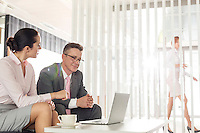 Businessman and businesswoman discussing in office