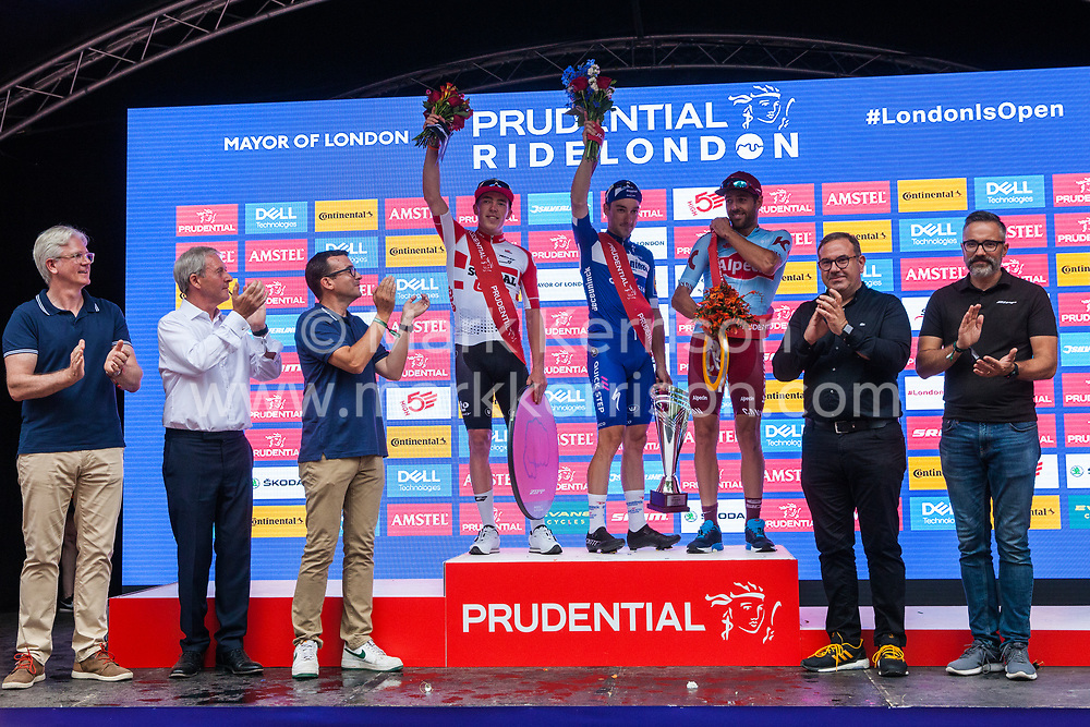 London, UK. 4 August, 2019. Elia Viviani of Deceuninck-Quick-Step stands on the podium after winning the Prudential RideLondon Classic with Alex Dowsett of Team Katusha Alpecin who won the King of the Mountains award and Stan Dewulf of Lotto Soudal who won the Combattivity award. The Prudential RideLondon Classic is Britain's only men's UCI WorldTour race and the richest one-day race in the world with a prize pot of 100,000 Euros on offer. This year's race features a redesigned race route from a start in Bushy Park in south-west London through Surrey, including a five-lap circuit of Box Hill, to a finish on the Mall.
