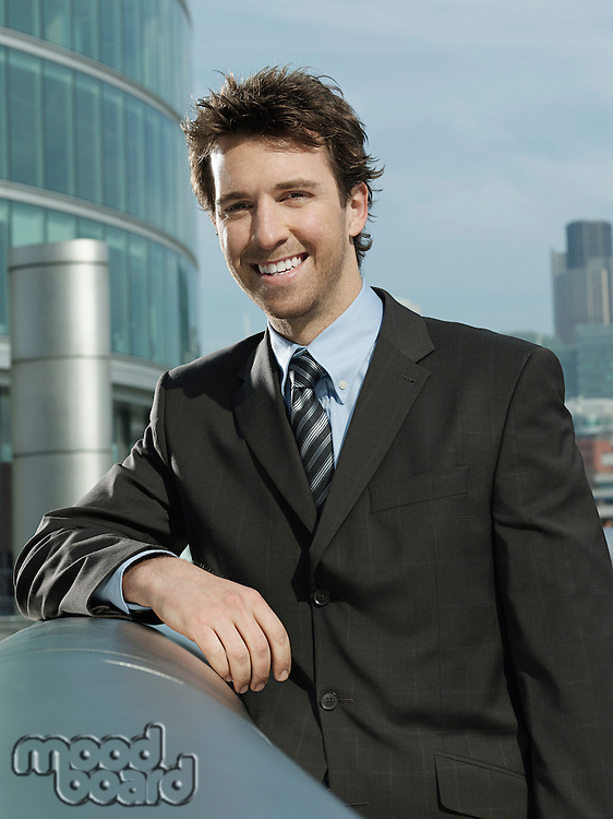 Young businessman leaning on pipe outside building smiling