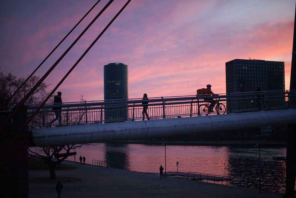 """Germany banned gatherings of more than 2 people called """"social distancing"""" because of the coronavirus. People crossing a bridge above river Main in Frankfurt which is very empty on a - normally very busy - Thursday evening."""