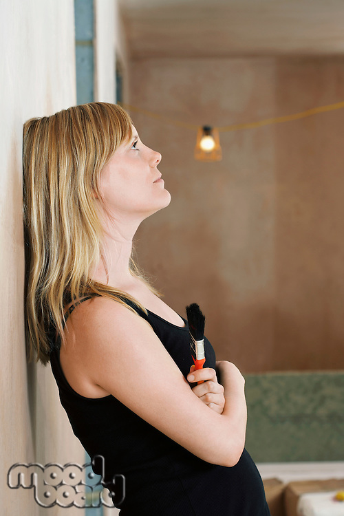 Pensive woman holding paint brush leaning against wall side view