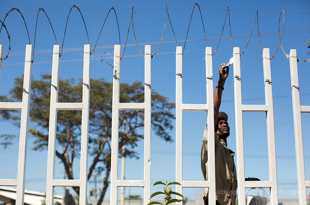 Painter Bertony Mezil touches up the fence at the Automeca vehicle dealership in Port-au-Prince, Haiti, January 5, 2015.  The hilly back lot of the business was taken over by displaced quake victims, quickly becoming a crowded tent camp. Bertony himself lived in a tent camp in another part of town for an entire year after the house he was renting in the Delmas neighborhood was destroyed in the disaster.