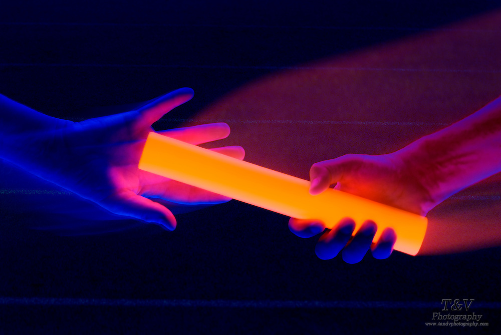 A baton is passed on a track field from one runner to another.Black light