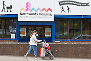 A woman walks past the office door of Northwards housing. Northwards housing have dramatically improved the energy rating to thousands of homes they manage for Manchester city council.