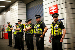 © Licensed to London News Pictures. 19/09/2014. Glasgow, UK. Police officers form a line outside Glasgow Queen Street station whilst pro-unionists and Scottish independence supporters being separated at George Square in Glasgow as Scotland decides to stay in the union and First Minister Alex Salmond resigns over the results of the Scottish independence referendum on Friday, 19 September 2014. Photo credit : Tolga Akmen/LNP