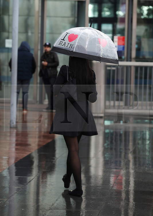 © Licensed to London News Pictures . 15/08/2013 . London, UK. A woman walks under the rain after a heavy shower falls in North Greenwich,London. Heavy rain is predicted for tomorrow in the city. Photo credit : /LNP