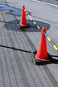 cones with yellow black bar blocking part of a road