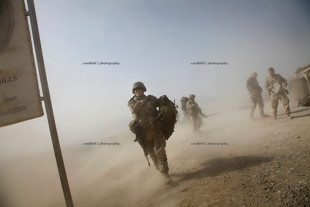A helicopter taken off covers german soldiers in a dust cloud at OP North, Northern Afghanistan