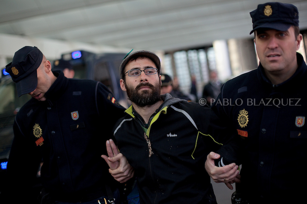 Riot police detain a member of the Mortgage Holder Platform (PAH) during a protest inside Atocha Train Station in Madrid, Spain, Tuesday, on March 19, 2013. Dozens of members of the Mortgage Holders Platform (PAH) wait for deputies arriving to Parliament demanding support for People's Legislative Initiative to stop evictions, allow social rent and debt relief.