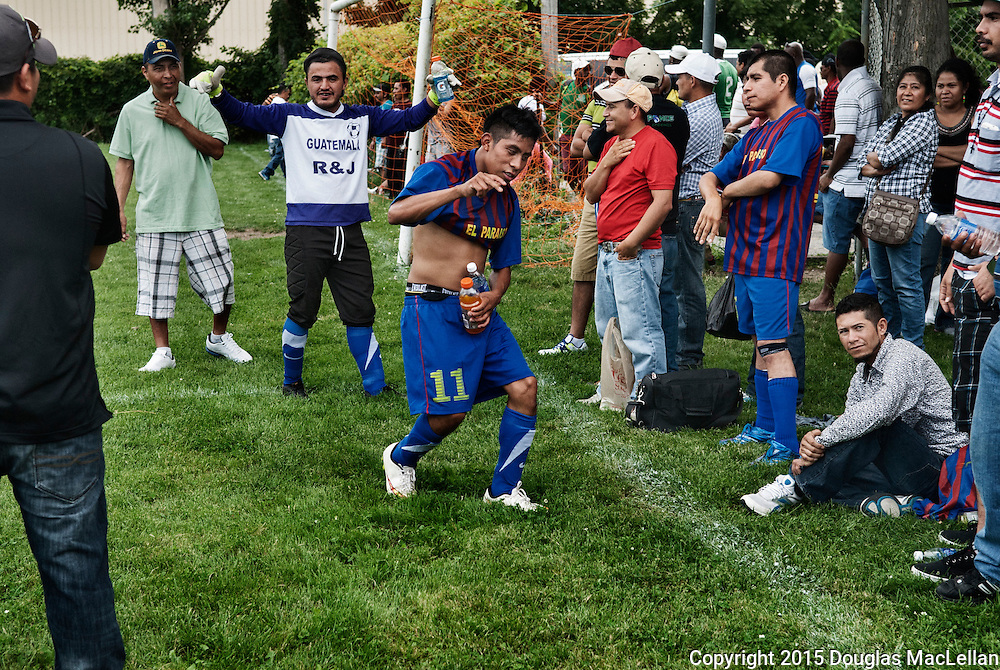 A player starts to take of his jersey during halftime of a soccer game. The league is operated by the greenhouse and farm owners. Most of the players are migrant workers.