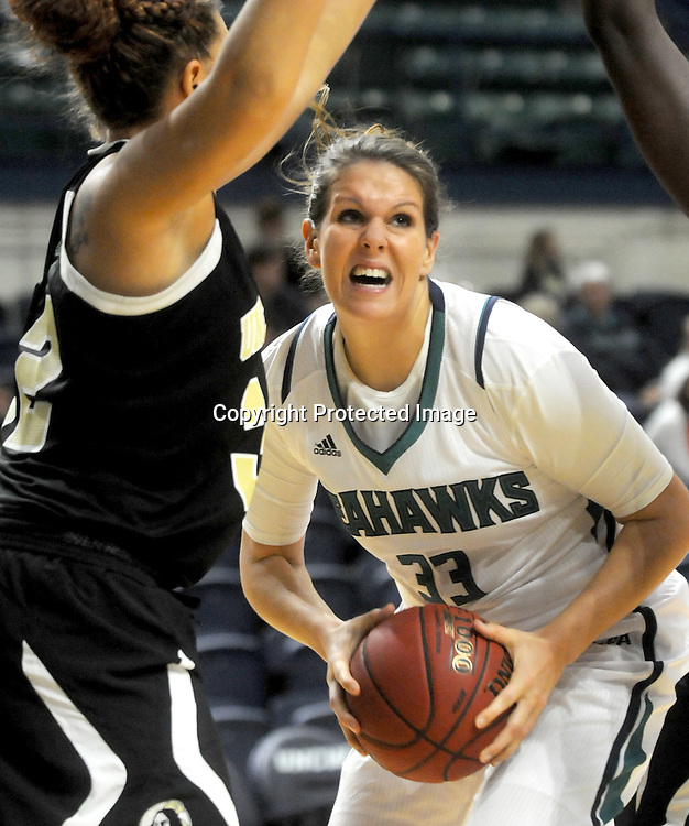 UNCW's Sarah Myatt drives on UNCP's Katelyn Mitchell Sunday November 16, 2014 at Trask Coliseum in Wilmington, N.C. (Jason A. Frizzelle)