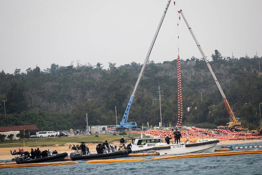 OKINAWA, JAPAN - JANUARY 20 : Workers use cranes to prepare the above-water float fencing to keep protest boats out of Henoko construction zone for the new U.S Marine Airbase in Oura Bay, Camp Schwab, Henoko, Nago, Okinawa, Japan on Janaury 20, 2017. The scheduled reclamation area for new the construction totals 160 hectares and will include 2 runways. Construction of the new base will require 21 million cubic meters of soil, enough to fill the Okinawa Prefectural Office 70 times, 17 million tons of which will be hauled in from Kyushu and Shikoku. (Photo by Richard Atrero de Guzman/ANADOLU Agency)