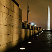 Washington Monument in the distance, with part of the National World War II Memorial in the foreground, at night