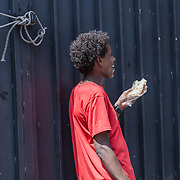 Quasi 800 profughi di cui più di 100 bambini vengono ospitati nella struttura di accoglienza Baobab di Via Cupa a Roma. La struttura può accogliere circa 220 migranti. Semplici cittadini e il gruppo SEL hanno raccolto generi alimentari da distribuire agli all'interno della struttura. Un ragazzo mangia un pezzo di pane.
