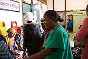 Sister Sulphine Twinomuhangi (in green) helps ladies whist they wait at Mulago Hospital, Uganda.