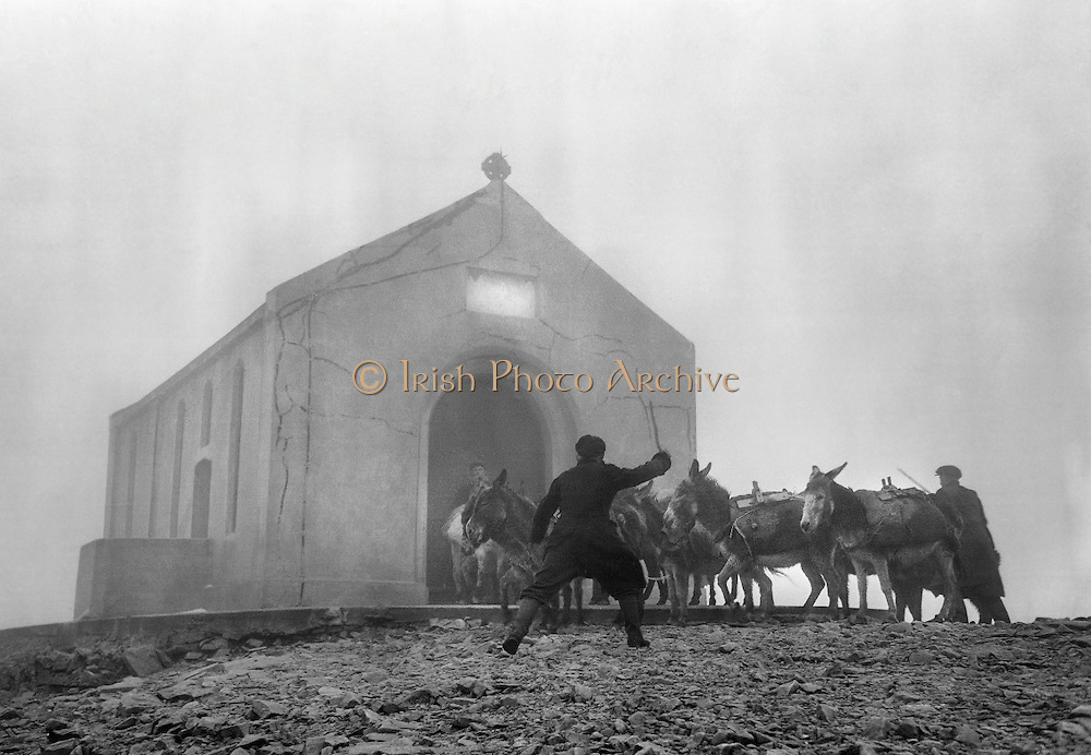 Donkeys bringing up the sand and cement for the exterior of the Oratory at the top of Croagh Patrick are urged on during a hailstorm..16.05.1962