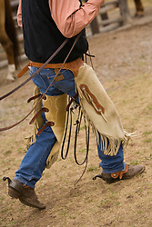 United States, Montana, Livingston, wrangler in chaps and boots with spurs walking across paddock