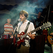 Bat Mitzvah boy plays electric guitar in smoky spotlight and sings at his reception