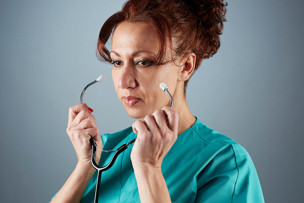 A portrait series representing the intense emotions that Doctors face.  A female Doctor wearing a stethoscope, and green medical scrub suit shown.