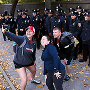 NYTRUN - NOV. 6, 2016 - NEW YORK - Foreground from left, Alicia Mitchell, Jacqueline Crisci, and Thomas Sandler, who came to cheer on Team RWB, a veterans organization, in the TCS New York City Marathon, stop along 5th Ave. across from the Solomon R. Guggenheim Museum (not visible) to take a selfie with New York City Police Officers on Sunday morning. Mitchell and Crisci are from Washington DC. Sandler is from Fredericksburg, Virginia. NYTCREDIT:  Karsten Moran for The New York Times