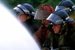 Stock photo of a four firemen spraying the hose during training