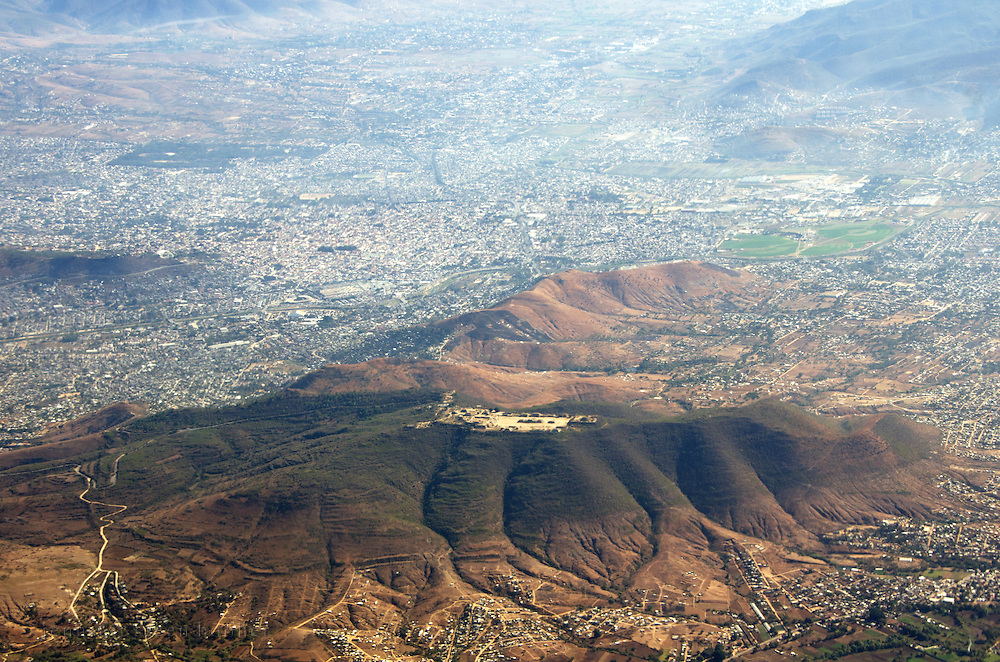 Aerial view of the ruins of Monte Alban (on top of the hill) with the city of Oaxaca de Juarez, Mexico, spreading around them.
