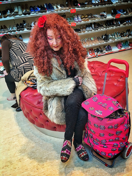 A woman waits for her daughter shopping for shoes at Cambridge city centre TKMaxx branch. The UK version of the outlet discount store known as TJMaxx in US.