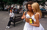 Two sexy girls pose for a photoshoot - a PR stunt for a womens' underwear company - employing their body services to promote their bras. A young boy looks on with a look of wonder and suspicion and workmen in the background look on with interest too.