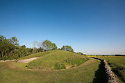 "Belas Knap is a neolithic long barrow, situated on Cleeve Hill, near Cheltenham and Winchcombe, in Gloucestershire, England. It is in the care of English Heritage. ""Belas"" is possibly derived from the Latin word bellus, 'beautiful', which could describe the hill or its view. ""Knap"" is derived from the Old English for the top, crest, or summit of a hill...What appears to be the main entrance to the barrow, with intricate dry-stone walling and large limestone jambs and lintels is, in fact, a false one. The actual burial chambers are down the long East and West sides of the barrow and at its Southern foot. There are four burial chambers, two on opposite sides near the middle, one at the South-East angle and one at the South end. These are formed of upright stone slabs, linked by dry-stone walling and originally had corbelled roofs...This northern end measures about 26 metres wide and the barrow then tapers towards the south where it measures 17 metres in width and less than a metre in height. The whole of this trapezoid mound is around 70 metres in length."