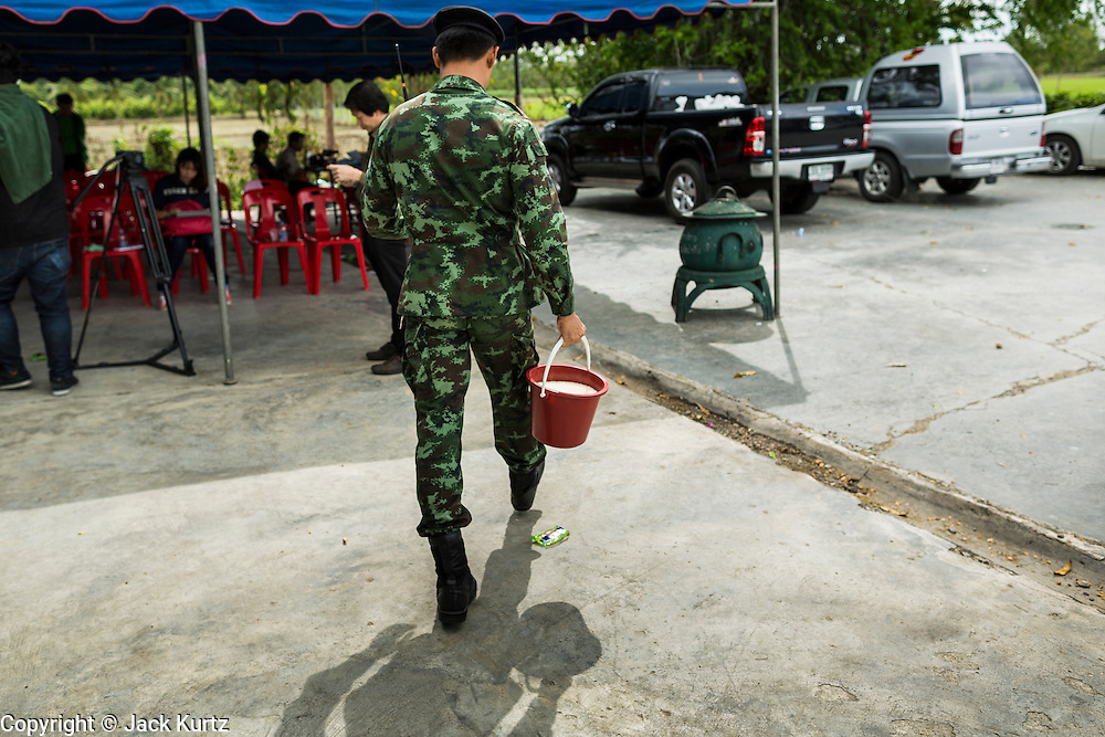"08 JULY 2014 - WANG NAM SAP, SUPHAN BURI, THAILAND:  A Thai soldier carries a bucket of rice to an inspection station at a rice warehouse in Wang Nam Sap, Suphan Buri province. Representatives of the Thai ruling junta have started inspecting stocks of rice bought by the ousted civilian government following the 2012 and 2013 rice harvests. The government of ousted former Prime Minister Yingluck Shinawatra bought up thousands of tons of rice from farmers at above market prices in one of its most controversial populist policies. The alleged mismanagement of the ""rice pledging scheme,"" as it was called, was one of the factors that lead to the May 2014 coup that ousted the government. According to officials doing the inspections found rotten and weevil-infested grain, along with evidence that large stocks were replaced with old or inferior grades.    PHOTO BY JACK KURTZ"