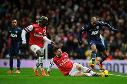 Man Utd Midfielder Ashley Young (ENG) is tackled by Arsenal Forward Olivier Giroud (FRA) - Photo mandatory by-line: Rogan Thomson/JMP - 07966 386802 - 12/02/14 - SPORT - FOOTBALL - Emirates Stadium, London - Arsenal v Manchester United - Barclays Premier League.