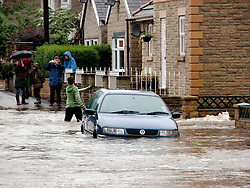 Locals wade through flood water at the junction of Mill Lane and The Common in Ecclesfield, Sheffield.15th June 2007.Image COPYRIGHT Paul David Drabble..