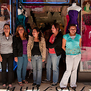 Women gather at the door of a local store selling quinceñera gowns in downtown Los Angeles, California. They have gathered to watch an immigrant rights march process down South Main Street, past the door of the shop, on March 27, 2009.  Photo by Jen Klewitz