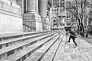 A young man rushes up the steps to the New York Public Libraryv