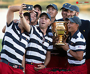 Oct 1, 2017; Jersey City, NJ, USA; U.S. Team golfer Justin Thomas takes a selfie with teammates Rickie Fowler and Daniel Berger and Jordan Spieth and Kevin Kisner and Dustin Johnson and Patrick Reed and Matt Kuchar with the championship trophy after The President's Cup golf tournament at Liberty National Golf Course. Mandatory Credit: Bill Streicher-USA TODAY Sports