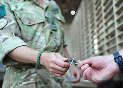 "© licensed to London News Pictures. HELMAND, AFG  21/04/11. A British Army chaplain from Sidmouth who is due to finish his tour this Easter Sunday has proved a hit with paratroopers in Helmand Province, handing out crosses made from the wire-mesh that surrounds their base. Padre Robin Richardson (40) a member of 3rd Battalion The Parachute Regiment, has been serving in Afghanistan for the last six months. ""Towards the beginning of the tour, some of the lads asked me if I had some crosses I could give them,"" he said. ""I found a few at Camp Bastion, and I gave them out. I ran out very quickly.""..""So I wandered around our camp at Shahzad, trying to find something I could fashion into a cross. I noticed some discarded Hesco wire, and I saw lots and lots of crosses"". The wire normally makes up part of the Hesco Bastion fortified walls,  mesh containers with thick liners filled with gravel - that surround military bases across Afghanistan. ""I got busy with some bolt-cutters and a hammer and a drill,"" said Robin. ""And I started making small crosses out of the discarded wire.""..""A lot of the lads have asked if they can have one,"" he said. ""And they've been wearing them, and understanding a bit about what lies behind it"". Robin will be returning home to be reunited with his family after six months. ""I've got three sons, aged 13, 11 and 7, and they're fab,"" he said. ""They give my heart a reason for beating every morning"". ""The thing I've missed the most has been their smiles"" he added. ""The first thing I'll do when I get home is give them a hug"".. Please see special instructions for usage rates. Photo credit should read SGT Alison Baskerville/LNP"