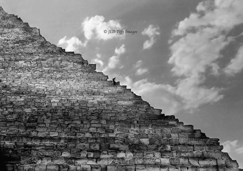 Great Pyramid, northeast corner, profile, one person descending seen in silhouette.  Dramatically cloudy sky, magical qualityh of sunlight on the huge blocks of the structure.  Diagonal of the slope is prominent.