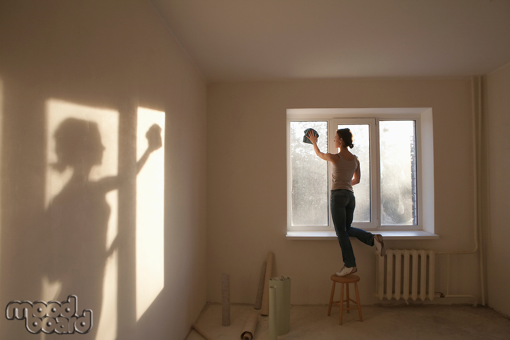 Woman cleaning windows in new apartment
